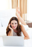 Beautiful woman on phone using her laptop Stock Photo