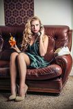 Beautiful woman phoning sitting on the sofa Royalty Free Stock Photography
