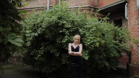 Beautiful woman photo model stands in green bushes in summer. Beautiful woman photo model stands in green bushes in summer stock footage