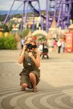 Beautiful woman photographer doing photos in an amusement park. A happy blogger makes a funny picture for his blog. Royalty Free Stock Image