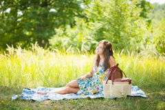 Beautiful woman at picnic. Beautiful young woman sitting on a blanket at picnic Stock Photos