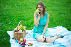 Beautiful woman with picnic basket eating fruits in summer park Stock Photography