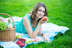 Beautiful woman with picnic basket and fruits in garden Royalty Free Stock Image