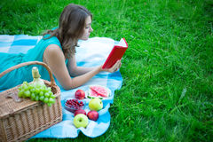 Beautiful woman with picnic basket and fruits reading book in ga Royalty Free Stock Images