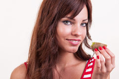 Beautiful woman with a piece of kiwi in her hand - healthy lifes Royalty Free Stock Photography