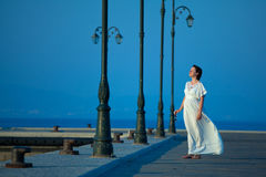 Beautiful woman on a pier. Happy beautiful woman on maxi white dress on a pier on a summer day Royalty Free Stock Image