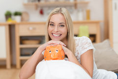 Beautiful woman with a piggy bank Stock Images