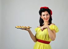 Beautiful woman  with yummy biscuits. Beautiful woman in pin up style with perfect hair and make up .Expressive facial expressions. Housewife with yummy Royalty Free Stock Photos