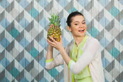 Beautiful woman with pineapple on a blue background. Beautiful woman with pineapple smile on a blue background. Happy girl hold ananas ready to make juice. Copy Royalty Free Stock Images