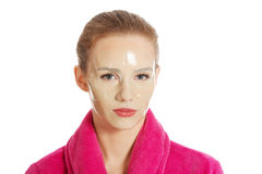 Beautiful woman in pink bathrobe and havinf facial mask. Stock Photo