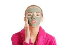 Beautiful woman in pink bathrobe and havinf facial mask. Stock Image