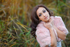 Beautiful woman in a pink cape walks in the park Stock Photography