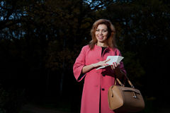 Beautiful woman in pink coat with book walks in the Park Royalty Free Stock Photos