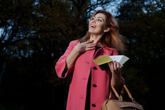 Beautiful woman in pink coat with book walks in th Royalty Free Stock Photography