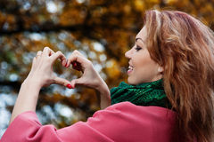 Beautiful woman in pink coat showing heart in the Park Royalty Free Stock Images