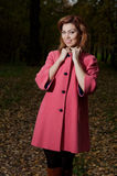 Beautiful woman in pink coat walks in the Park Stock Photography