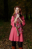 Beautiful woman in pink coat walks in the Park Stock Photos