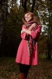 Beautiful woman in pink coat walks in the Park Stock Photo