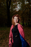 Beautiful woman in pink coat walks in the Park Royalty Free Stock Photo