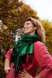 Beautiful woman in pink coat walks in the Park Stock Images
