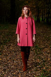 Beautiful woman in pink coat walks in the Park Royalty Free Stock Images