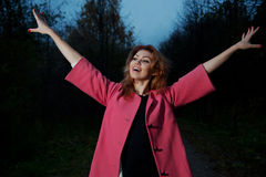 Beautiful woman in pink coat walks in the Park Royalty Free Stock Photos