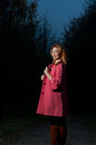 Beautiful woman in pink coat walks in the Park at evening Stock Images