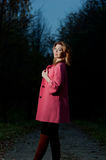 Beautiful woman in pink coat walks in the Park at evening Royalty Free Stock Photography