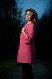 Beautiful woman in pink coat walks in the Park at evening Stock Photography