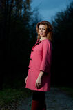 Beautiful woman in pink coat walks in the Park at evening Royalty Free Stock Photos