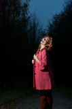 Beautiful woman in pink coat walks in the Park at evening Royalty Free Stock Photo