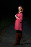 Beautiful woman in pink coat walks in the Park at evening Royalty Free Stock Image