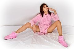 Beautiful woman in pink cosy sleepwear on the bed. Stock Image