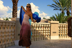 Beautiful woman pink dress blue veil. A beautiful shapely blonde woman in sunglasses wearing a lonk pink dress and holding a blue silk veil behind her outdoors Royalty Free Stock Images