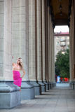 Beautiful woman in pink dress among columns. Stock Images