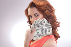 A beautiful woman in a pink dress with dollar banknotes in the hands. Christmas, x-mas, sale, banking concept - smiling woman in red dress with us dollar money Stock Photos