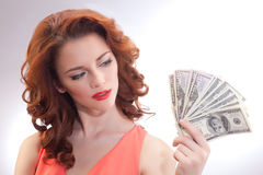 A beautiful woman in a pink dress with dollar banknotes in the hands Stock Image