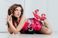 Beautiful woman in pink dress enjoys vintage phone Royalty Free Stock Photo