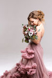 Beautiful woman in a pink dress posing with a bouquet. stock photos