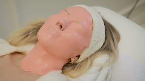 Beautiful woman with pink facial mask at beauty salon. Spa treatment.