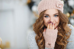 Beautiful woman in pink hat near Christmas tree Royalty Free Stock Images