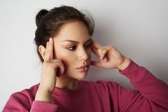 Beautiful woman in pink hoody with a severe headache with the hands in the head over white empty wall on background. Beauty and healthcare concept Stock Photos