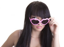 Beautiful woman in pink party glasses. Looking curiously Royalty Free Stock Images