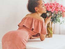 Beautiful woman with pink peonies. Lifestyle photo of beautiful young woman with pink peonies. Bouquet as gift. Emotions of happiness and joy. Valentines day Royalty Free Stock Photo