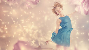 Beautiful woman in a pink peony flower fantasy. Beautiful woman in a blue dress in a pink peony flower fantasy Stock Photo