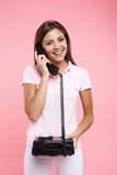 Beautiful woman in pink polo making phonecall. Portrait of beautiful woman in pink polo making phonecalls, with old balck landline, looking straight Royalty Free Stock Photography