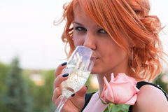 Beautiful woman with pink rose drinking champagne Royalty Free Stock Image