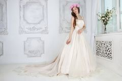 Beautiful woman in pink roses wreath and in long dress. Poses in white studio Royalty Free Stock Photo