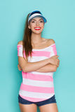 Beautiful Woman In Pink Striped Shirt And Sun Visor. Smiling beautiful young woman in pink striped shirt, blue sun visor and jeans shorts standing with arms Stock Photo