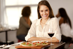 Beautiful woman in a pizza restaurant. Portrait of a beautiful young woman looking to camera in a pizza restaurant Royalty Free Stock Image